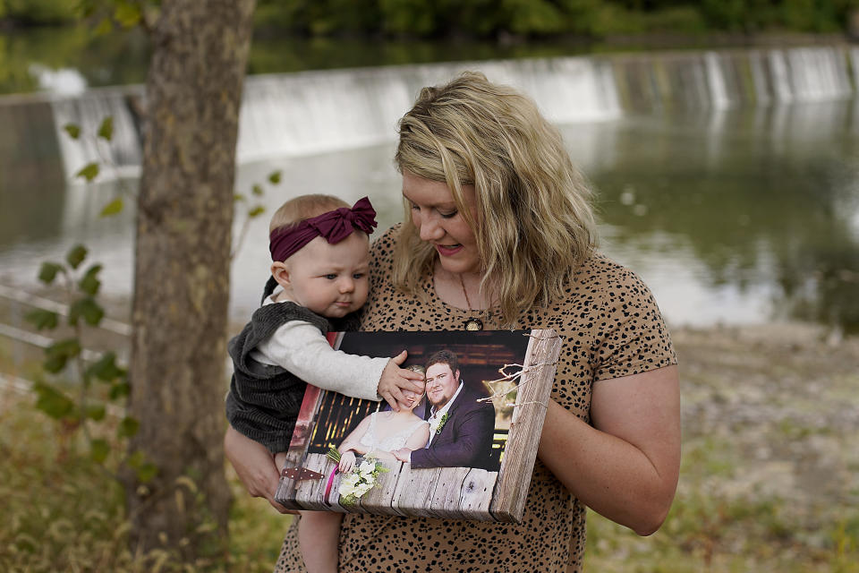 Aubrea Baker displays her wedding photo as she and her 7-month-old daughter Haylen visit one of her late husband's favorite fishing spots Saturday, Oct. 2, 2021, in Burlington, Kan. Her husband, Danny Baker, was among the 700,000 U.S. victims of COVID-19, dying on Sept. 14, after testing positive in July. (AP Photo/Charlie Riedel)