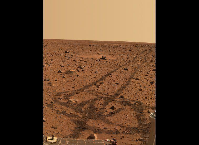 """While driving over the reddish rocks and soils of Mars, the rover's wheels dig below the thin dusty layer and reveal darker, brownish soils just below. The circular tracks are """"pirouettes"""" that the rovers occasionally do to align their radio antennas for best possible communications. <em>Spirit rover, Pancam image, mission sol (martian day) 141 (May 26, 2004). From """"Postcards from Mars"""" by Jim Bell; Photo credit: NASA/JPL/Cornell University</em>"""