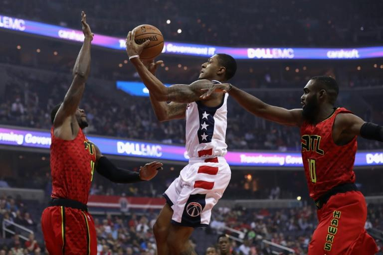 Bradley Beal of the Washington Wizards puts up a shot in front of Paul Millsap (L) and Tim Hardaway Jr. of the Atlanta Hawks in Game Five of the Eastern Conference quarter-finals during the 2017 NBA Playoffs, in Washington, DC, on April 26
