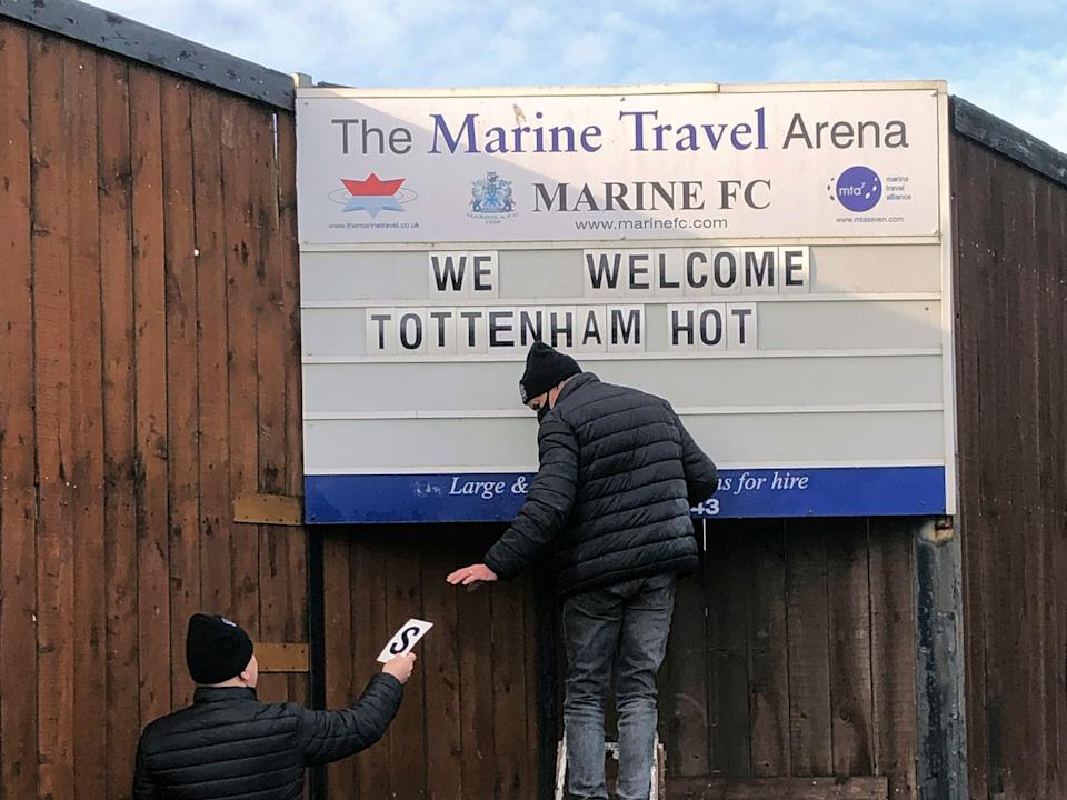 Volunteers hang up letters welcoming Tottenham Hotspur ahead of their FA Cup match (AP)