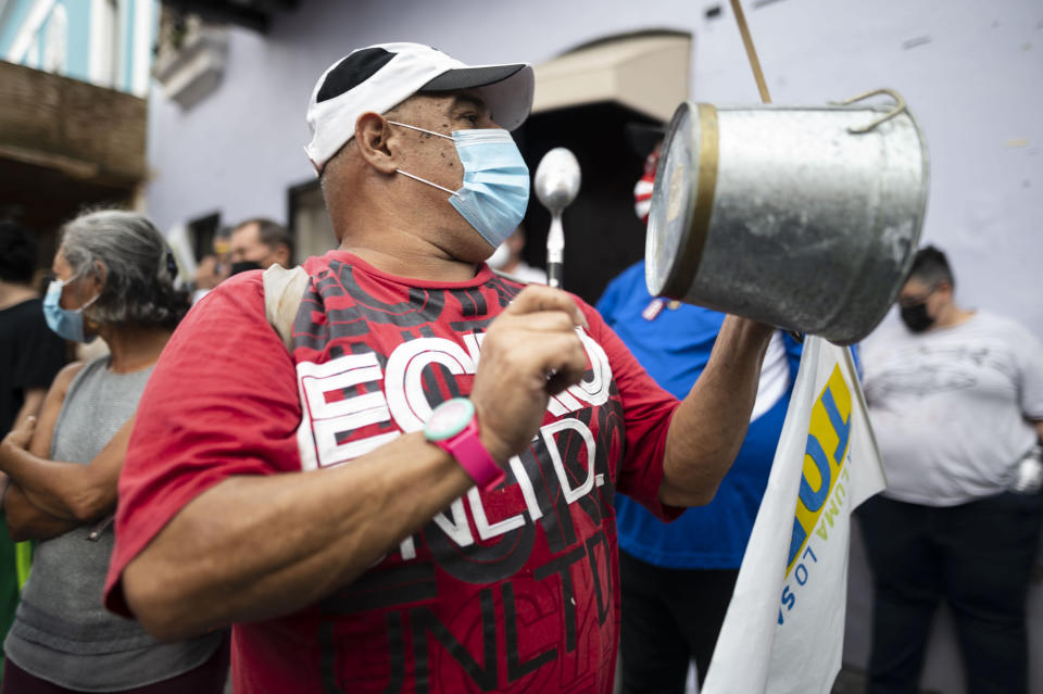 Demonstrators from various organizations congregate on Fortaleza street to protest against the constant selective blackouts that the island has suffered for weeks due to low power generation, in San Juan, Puerto Rico, Friday, Oct. 1, 2021. Power outages across the island have surged in recent weeks, with some lasting up to several days. (AP Photo/Carlos Giusti)
