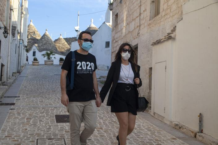 A couple wear masks in Alberobello, Italy. (Getty Images)