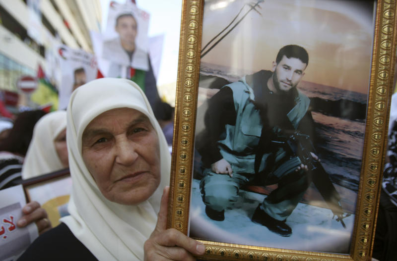A Palestinian woman holds a photograph of a prisoner jailed in Israel, during a rally marking the annual prisoners' day in the West Bank city of Nablus, Tuesday, April 17, 2012. The Israeli prison service said Tuesday hundreds of Palestinian prisoners have launched a hunger strike to mark the Palestinians' annual prisoners day. (AP Photo/Nasser Ishtayeh)