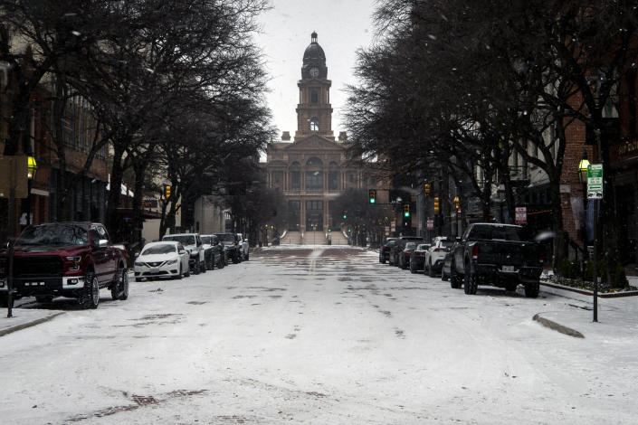 Snow is shown along Main Street near the Tarrant County Courthouse in Fort Worth, Texas, Sunday, Feb. 14, 2021.  / Credit: Yffy Yassifor/Star-Telegram via AP