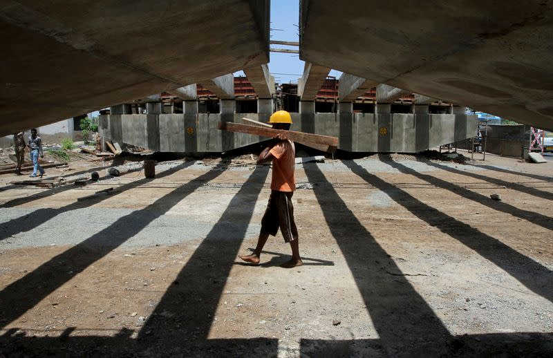 A worker carries pieces of wood at the construction site of a flyover bridge in Chennai