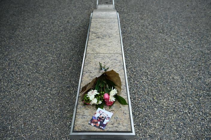 Flowers are left next to a picture on a bench.
