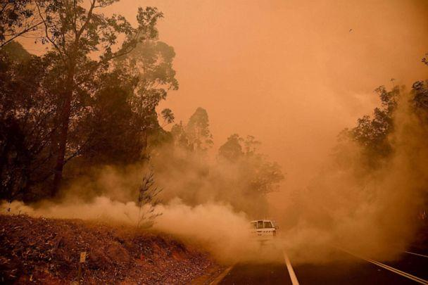 PHOTO: Firefighters tackle a bushfire in thick smoke in the town of Moruya, south of Batemans Bay, in New South Wales, Australia, on Jan. 4, 2020. (AFP via Getty Images)