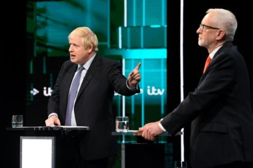 A handout picture taken and released by ITV shows  Britain's Prime Minister Boris Johnson (L) and Britain's Labour Party leader Jeremy Corbyn (R) as they debate in Manchester