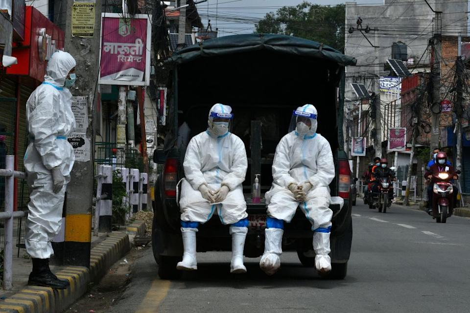 Nepal army wearing personal protective equipment (PPE) suits in a vehicle as they wait to transport the body of a person who died from Covid-19 coronavirus to a crematorium in Kathmandu.