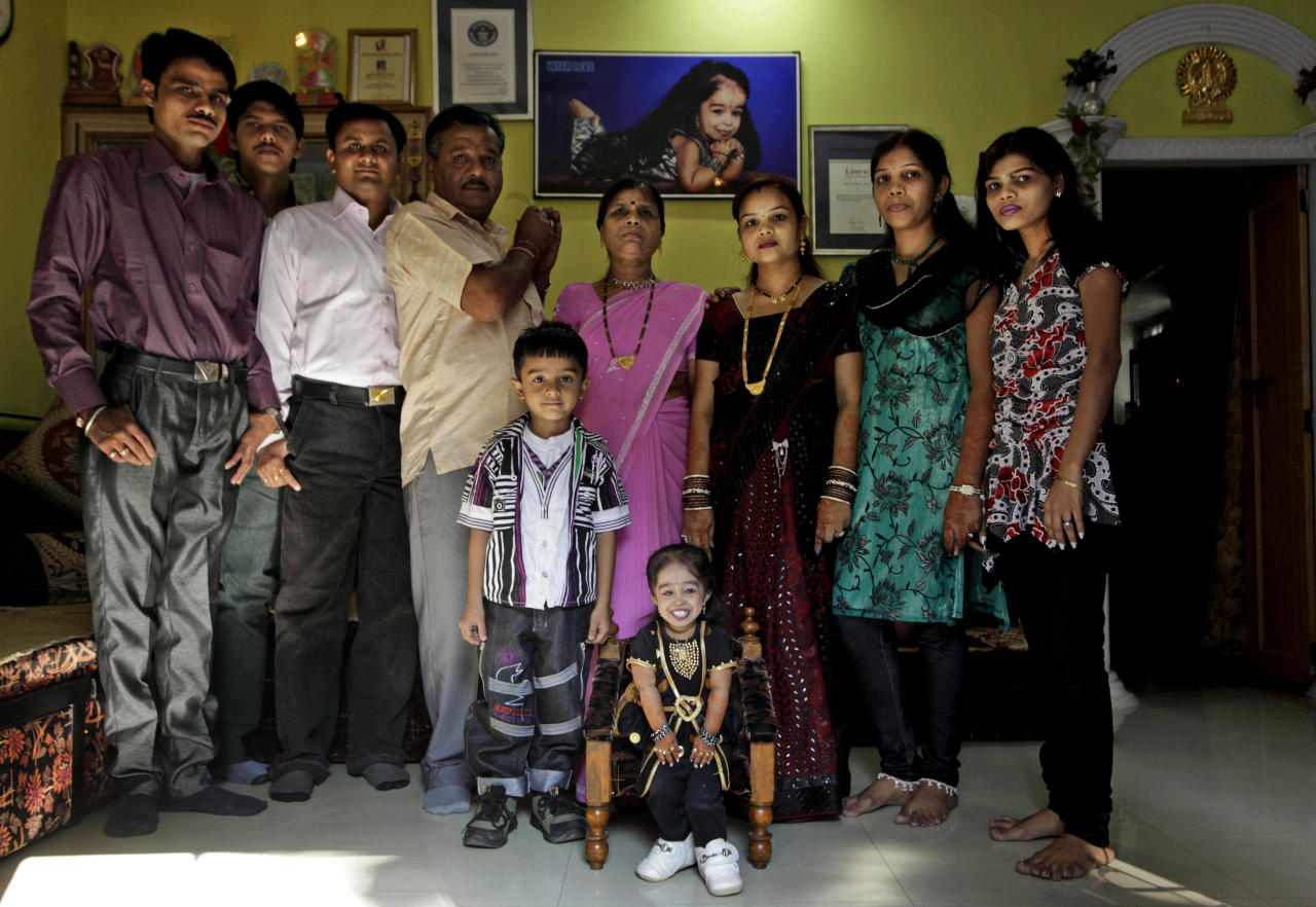 Jyoti Amge, 18, center, who stands at 61.95 centimeters (2 feet), poses for a photography with her family at her residence before a press conference with the Guinness World Records in Nagpur, India, Friday, Dec. 16, 2011. Officials from Guinness were expected to measure Amge later Friday and declare her the World's Shortest Woman. (AP Photo/Manish Swarup)