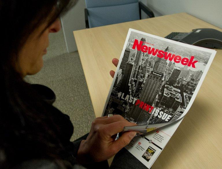 A woman perusing the final print edition of Newsweek in Washington, DC on December 24, 2012