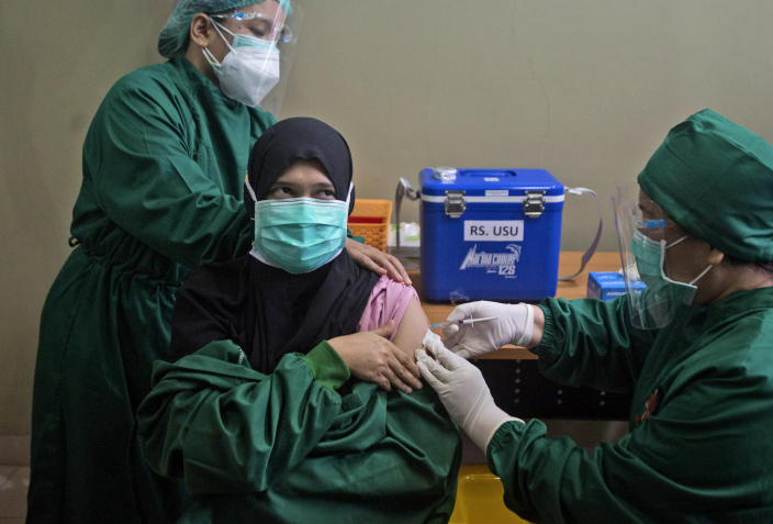 FILE - In this Wednesday, Jan. 20, 2021 file photo, Dr. Lili Rahmawaty, right, gives a shot of COVID-19 vaccine to a colleague at North Sumatra University Hospital in Medan, North Sumatra, Indonesia. The choices are limited for Indonesia, the world's fourth most populous country, and many other low- and middle-income countries clobbered by COVID. Vaccine deployment globally has been dominated by rich countries, which have snapped up 5.4 billion of the 7.8 billion doses purchased worldwide, according to Duke University. (AP Photo/Binsar Bakkara)