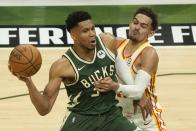 Milwaukee Bucks' Giannis Antetokounmpo tries to get past Atlanta Hawks' Trae Young during the first half of Game 1 of the NBA Eastern Conference basketball finals game Wednesday, June 23, 2021, in Milwaukee. (AP Photo/Morry Gash)