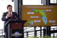 FILE - In this Wednesday, June 3, 2020 file photo, Gov. Ron DeSantis speaks at a news conference at Universal Studios in Orlando, Fla., as the theme park reopened for season pass holders and will open to the general public two days later. As of August 2020, the state has had more than half a million confirmed cases and 35,000 hospitalizations, yet DeSantis still hasn't issued a mask mandate. Some local governments have. (AP Photo/John Raoux)