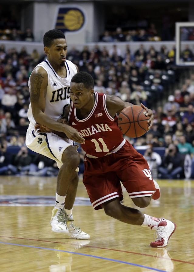 Indiana guard Yogi Ferrell, right, drives on Notre Dame guard Eric Atkins in the second half of an NCAA college basketball game in Indianapolis, Saturday, Dec. 14, 2013. Notre Dame defeated Indiana 79-72. (AP Photo/Michael Conroy)