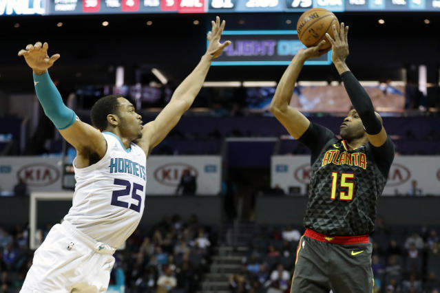 Atlanta Hawks' Vince Carter (15) aims his jumper over Charlotte Hornets' P.J. Washington (25) during the second half of an NBA basketball game in Charlotte, N.C., Sunday, Dec. 8, 2019. The Hawks won 122-107. (AP Photo/Bob Leverone)