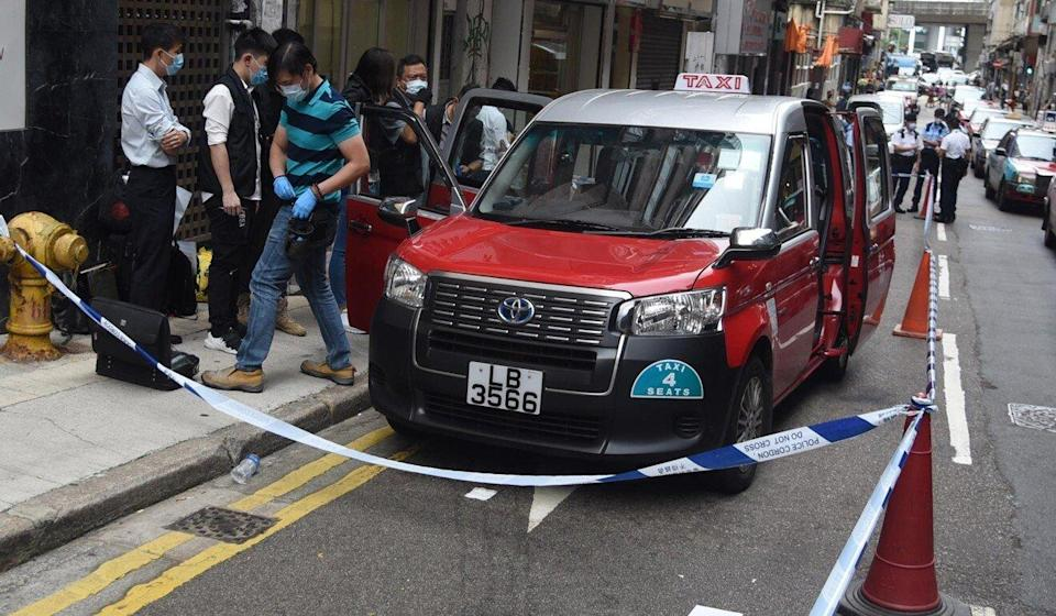 Police officers investigate the killing of a taxi driver in Sai Wan on Tuesday. Photo: Handout