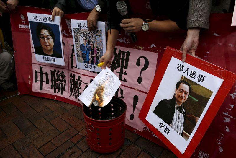 A pro-democracy demonstrator burns a letter next to pictures of missing staff members of a publishing house and a bookstore during a protest to call for an investigation behind their disappearance, outside the Chinese liaison office in Hong Kong