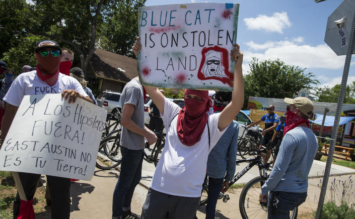Activists hold signs up signs during protest against Blue Cat Cafe in Austin, Texas, in June 2017. The Jumpolin pinata store previously at the location was torn down. (Photo: Nick Wagner/Austin American-Statesman via AP)