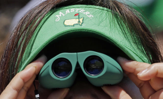 A spectator watches competitors during the first round of the Masters golf tournament Thursday, April 10, 2014, in Augusta, Ga. (AP Photo/David J. Phillip)