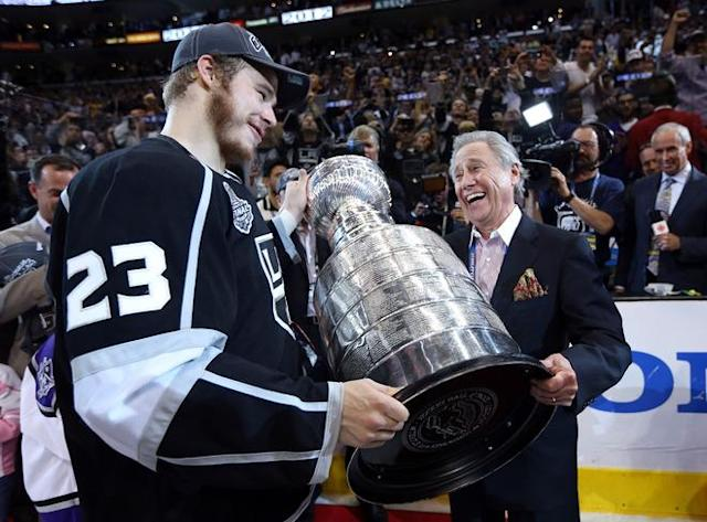 LOS ANGELES, CA - JUNE 11: Captain Dustin Brown #23 of the Los Angeles Kings hands the Stanley Cup to team owner Philip Anschutz after the Kings defeated the New Jersey Devils 6-1 to win the Stanley Cup in Game Six of the 2012 Stanley Cup Final at Staples Center on June 11, 2012 in Los Angeles, California. (Photo by Bruce Bennett/Getty Images)
