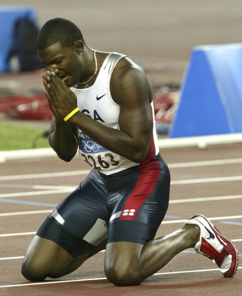 "FILE - In this Aug. 22, 2004, file photo, Justin Gatlin, of the United States, reacts after winning the gold in the 100-meters at the Olympic Stadium during the 2004 Olympic Games in Athens. At rock bottom, American sprinter Justin Gatlin thought about wrapping his car around a tree because, ""no one is going to miss me.""  (AP Photo/Vincent Thian, File)"