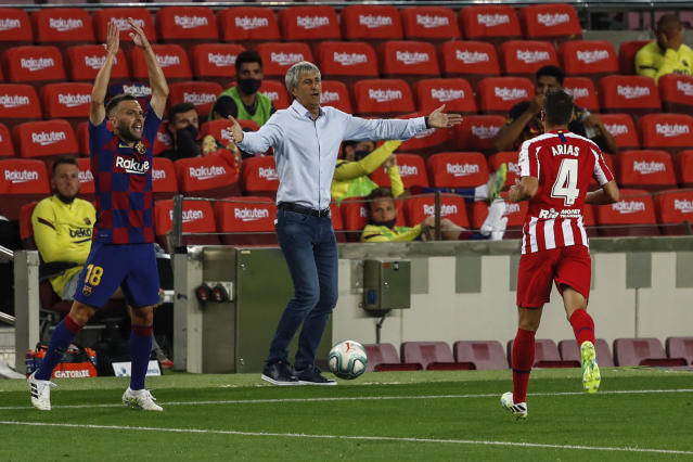 Barcelona's head coach Quique Setien, center, gestures during the Spanish La Liga soccer match between FC Barcelona and Atletico Madrid at the Camp Nou stadium in Barcelona, Spain, Tuesday, June 30, 2020. (AP Photo/Joan Monfort)