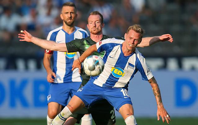 Maximilian Arnold from VfL Wolfsburg, center, and Berlin's Ondrej Duda, front, battle for the ball during the German Bundesliga soccer match between VfL Wolfsburg and Hertha BSC Berlin in Berlin, Germany, Sunday, Aug. 25, 2019. (Andreas Gora/dpa via AP)