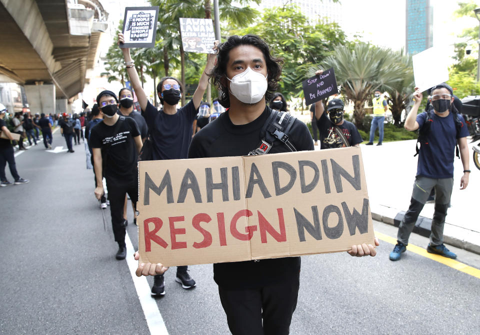A protester holds placard during a demonstration demanding the prime minister step down near the Independence Square in Kuala Lumpur, Saturday, July 31, 2021. Hundreds of black-clad Malaysian youths have rallied in the city center, demanding Prime Minister Muhyiddin Yassin resign for mismanaging the coronavirus pandemic that has worsened. (AP Photo/FL Wong)