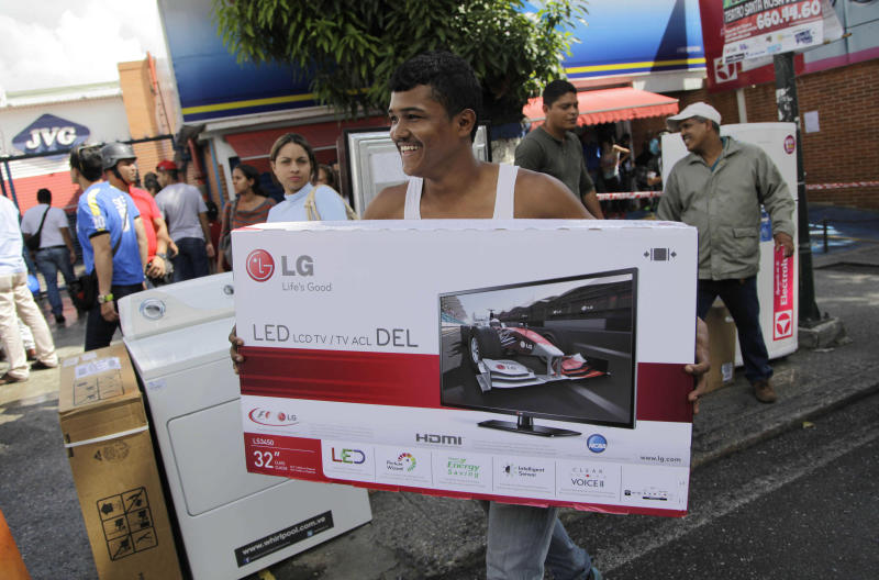 "A man carries his newly purchased television outside an appliance store in Caracas, Venezuela, Monday, Nov. 11, 2013. President Nicolas Maduro seized control of a nationwide chain of appliance stores Friday seeking to battle inflation and shortages. Shoppers were still arriving Monday to join the hundreds who began amassing over the weekend after price inspectors said they found evidence of ""usury"" and Maduro ordered the chain Tiendas Daka ""occupation."" (AP Photo/Ariana Cubillos)"