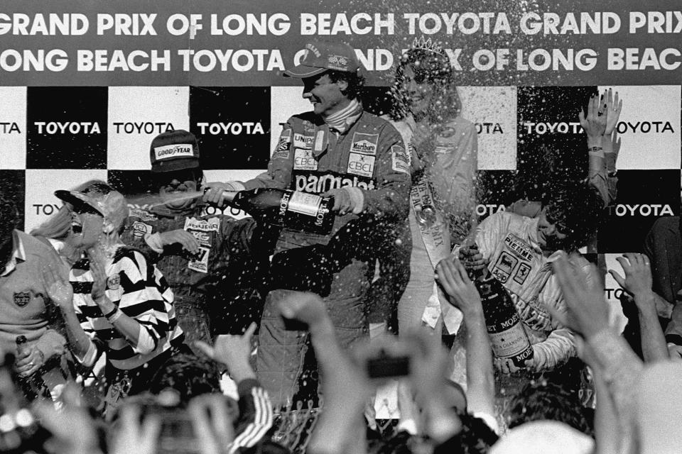 FILE - Two-time Formula 1 world champion Niki Lauda, center, sprays champagne over well wishers around the winner circle at the Grand Prix circuit in Long Beach, Calif., in this April 5, 1982, file photo. Lauda, driving for Team McLaren, won the race, finishing ahead of Team Williams driver Keke Rosberg, left, of Finland, second, and Canadian Gilles Villeneuve, right, who finished third driving for Ferrari. The Grand Prix of Long Beach opens 17 months after the pandemic ended the crown jewel's streak as one of the longest continuously-running street events in racing. (AP Photo/FIle)
