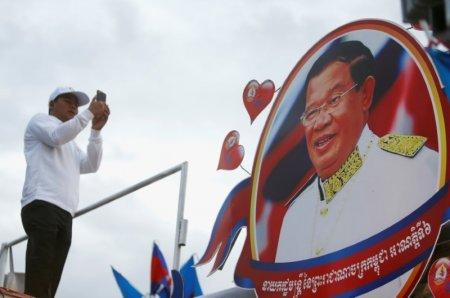 A supporter of the ruling Cambodian People's Party (CPP) uses a mobile phone to photograph a portrait of CPP president Hun Sen during an election campaign in Phnom Penh, Cambodia, July 7, 2018. REUTERS/Samrang Pring