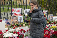 A woman reacts as she lays a flower at a symbolic memorial of victims of the military conflict in the separatist region of Nagorno-Karabakh at the Armenian Embassy in Moscow, Russia, Saturday, Oct. 17, 2020. Nagorno-Karabakh lies within Azerbaijan but has been under the control of ethnic Armenian forces backed by Armenia since a war there ended in 1994. The latest outburst of fighting began on Sept. 27 and has involved heavy artillery, rockets and drones, killing hundreds and marking the largest escalation of hostilities between the South Caucasus neighbors in more than a quarter-century. (AP Photo/Mikhail Kirakosyan)