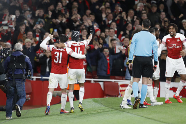 Arsenal's Pierre-Emerick Aubameyang, center, celebrates after scoring his side's third goal during the Europa League round of 16, 2nd leg, soccer match between Arsenal and Rennes at the Emirates stadium in London, Thursday, March 14, 2019. (AP Photo/Alastair Grant)