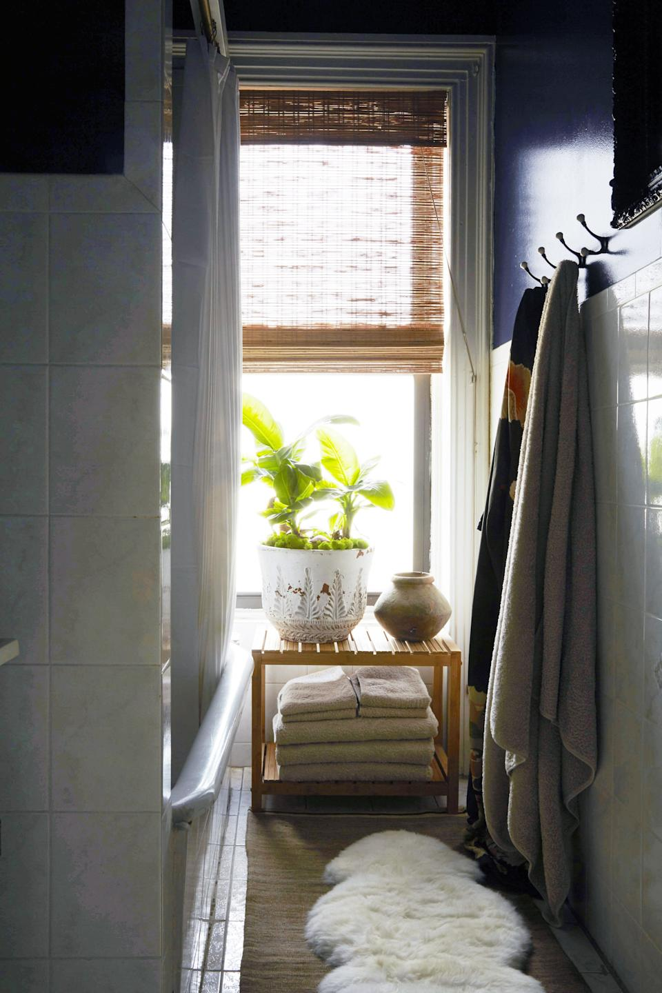 A light-filled, narrow bathroom is accented with a sheepskin rug and bamboo roller blinds in the Brooklyn home of designers Casey Kenyon and Jonathon Beck.