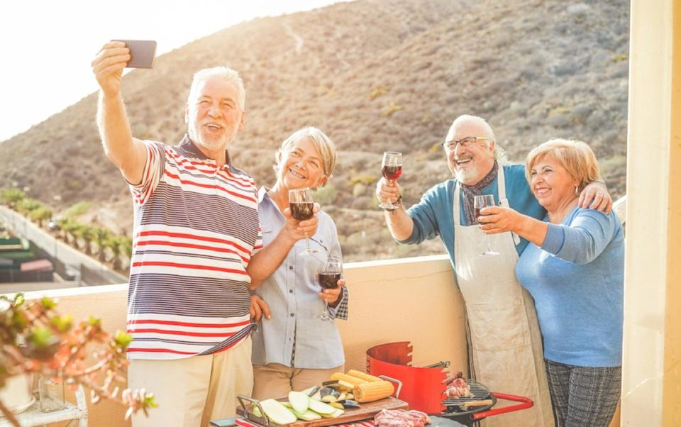 older couples taking photo while drinking wine, over 50 regrets