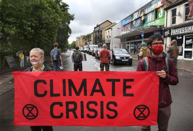 Protesters hold a banner saying climate crisis during the demonstration in Cambridge (Photo: SOPA Images via Getty Images)