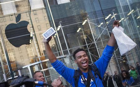One of the first customers to purchase the Apple iPhone 5S celebrates after exiting the Apple Retail Store on Fifth Avenue in Manhattan, New York September 20, 2013. Apple Inc's newest smartphone models hit stores on Friday in many countries across the world, REUTERS/Adrees Latif