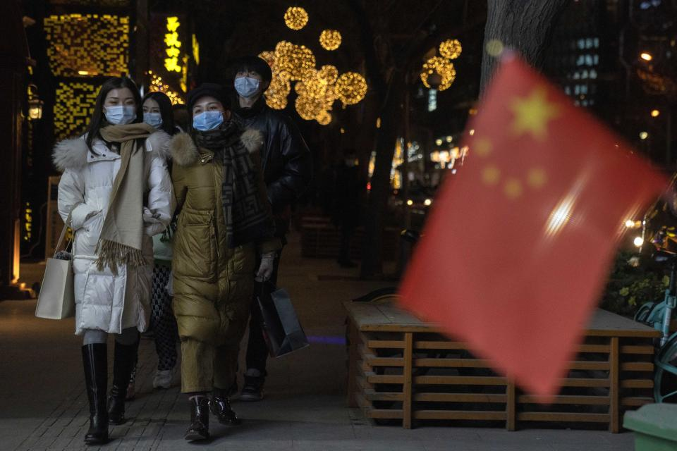 Patrons wearing masks to protect from the coronavirus past by a Chinese national flag as they visit a bar street on New Year Eve in Beijing on Thursday, Dec. 31, 2020. This New Year's Eve is being celebrated like no other, with pandemic restrictions limiting crowds and many people bidding farewell to a year they'd prefer to forget. (AP Photo/Ng Han Guan)