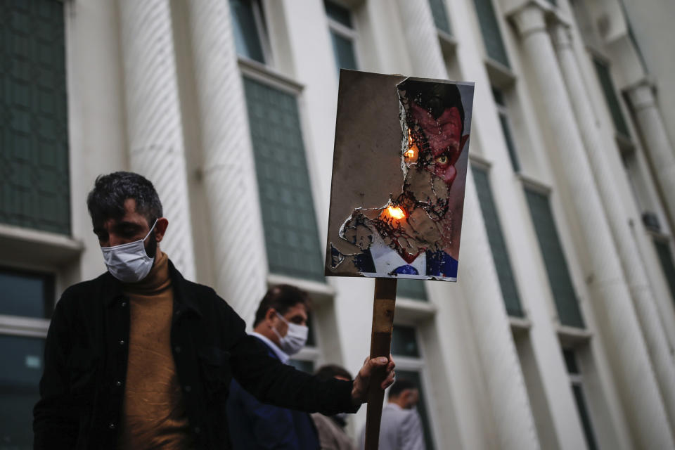 A man holds a poster with a caricature of France's President Emmanuel Macron, depicting him as a devil, which was set on fire, during a protest against France in Istanbul, Friday, Oct. 30, 2020. There is ongoing tension between France and Turkey after Turkish President Recep Tayyip Erdogan said Macron needed mental health treatment and made other comments that the French government described as unacceptably rude. Erdogan questioned his French counterpart's mental condition while criticizing Macron's attitude toward Islam and Muslims. (AP Photo/Emrah Gurel)