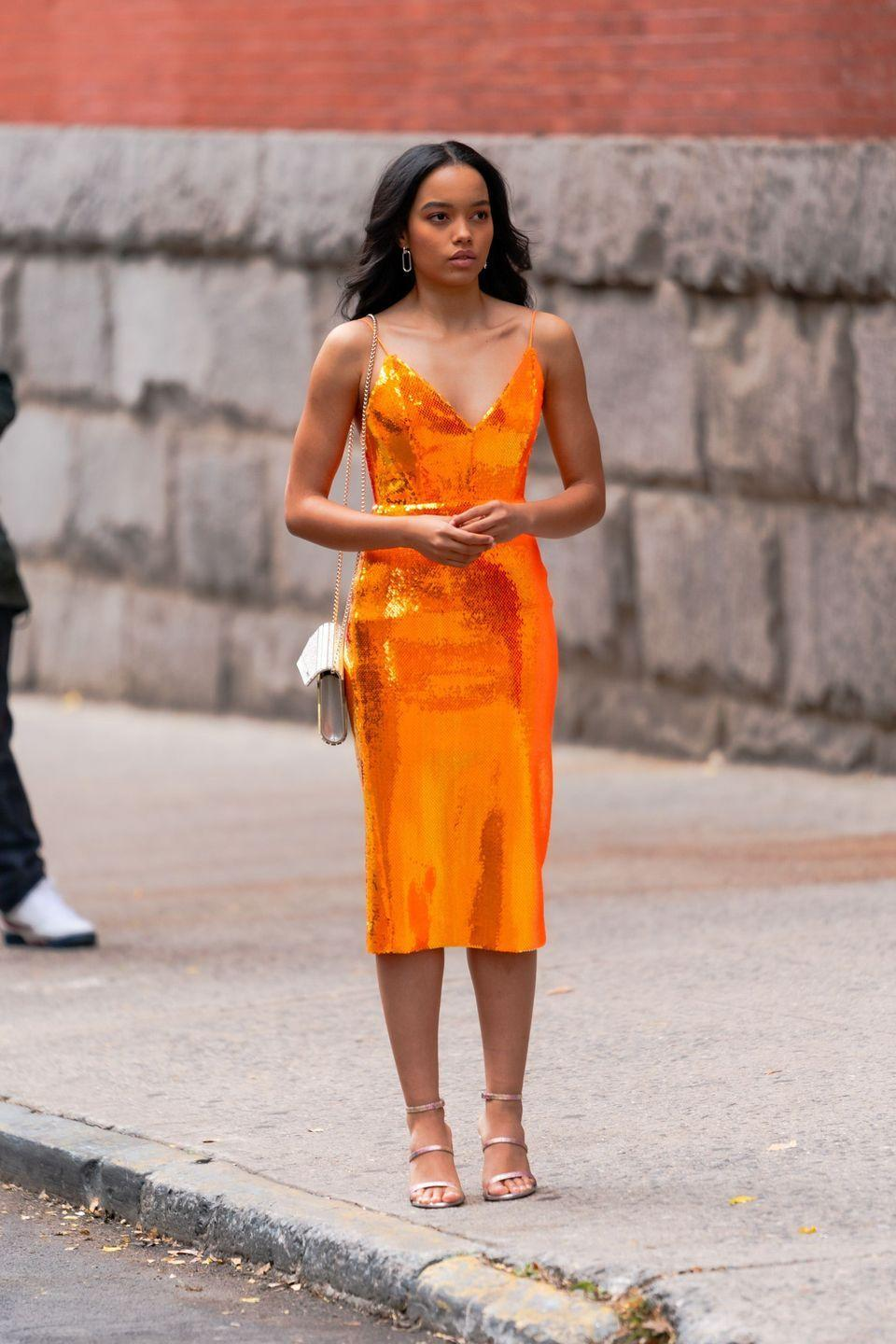<p>Whitney Peak glitters in an orange sequined dress and strappy heels. </p>