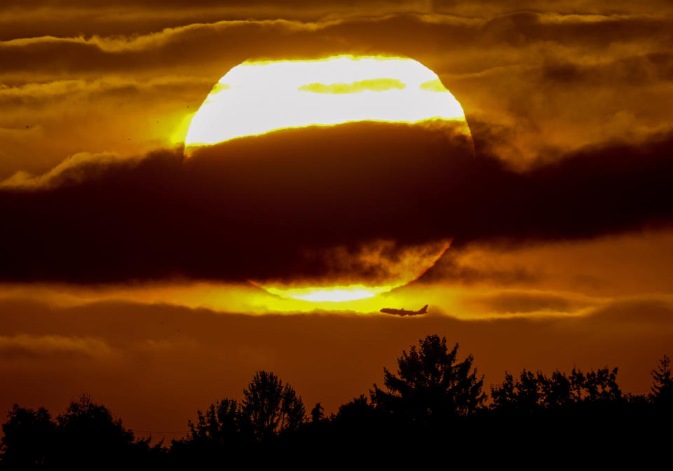 The sun rises over a forest as a plane passes by in Frankfurt, Germany, Wednesday, Oct. 6, 2021. (AP Photo/Michael Probst)
