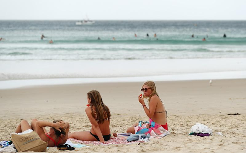 Three women in bikinis shows sitting on a beach on the Gold Coast.