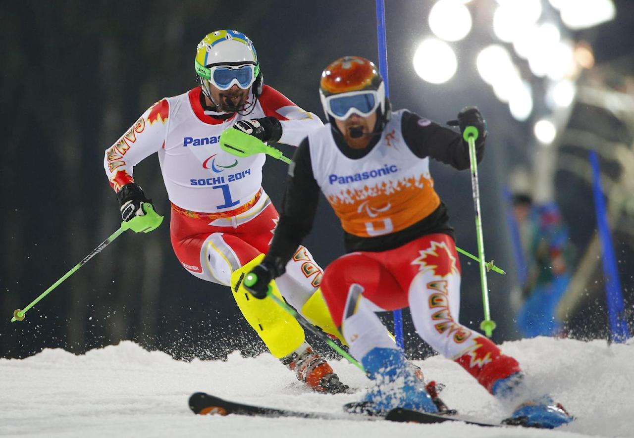 Chris Williamson of Canada, left, and his guide Nick Brush compete during the men's alpine skiing, slalom, visually impaired event at the 2014 Winter Paralympic, Thursday, March 13, 2014, in Krasnaya Polyana, Russia. (AP Photo/Dmitry Lovetsky)
