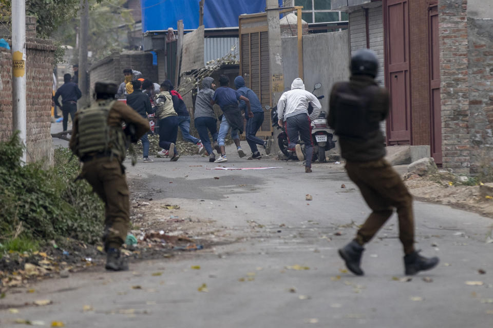 Indian police men fire pellets as they chase Kashmiri protestors near the site of a gun battle on the outskirts of Srinagar, Indian controlled Kashmir, Sunday, Nov. 1, 2020. According to police, Indian government forces killed Saifullah Mir, a top rebel commander of the region's largest rebel group, Hizbul Mujahideen which has spearheaded an armed rebellion against Indian rule for decades. (AP Photo/ Dar Yasin)