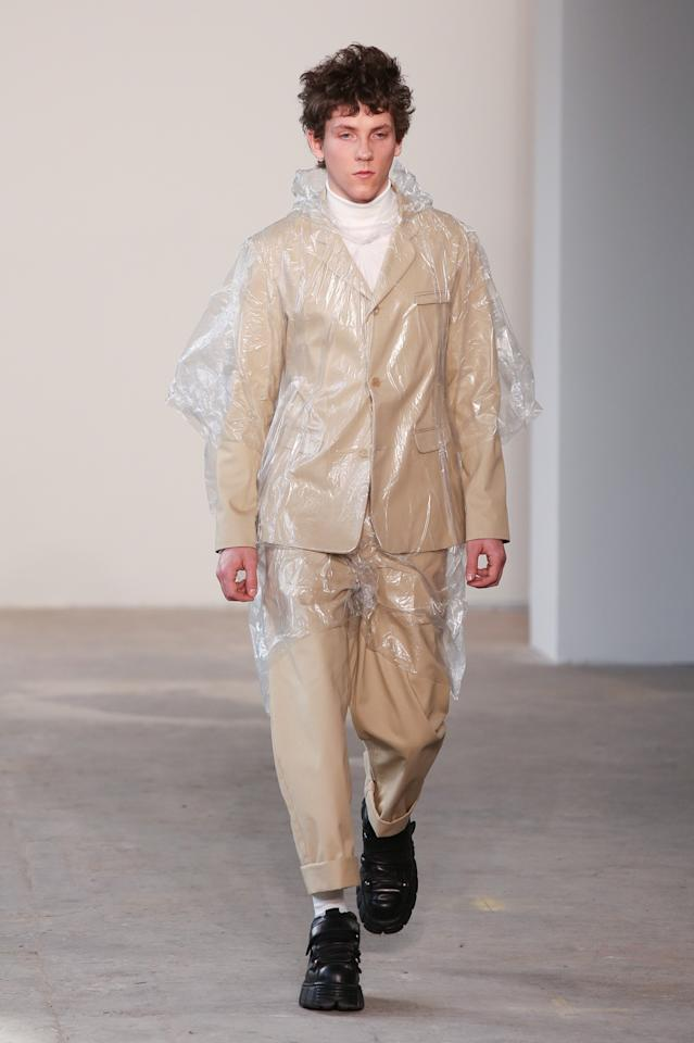 <p>A new look for fall? Patrik Ervell shows us that you can wear a plastic poncho over your suit and still look stylish. <i>(Photo: Getty)</i> </p>