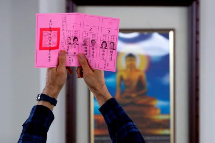 An election official shows a ballot with vote for Taiwan President Tsai Ing-wen as votes are counted at a polling station in Taipei