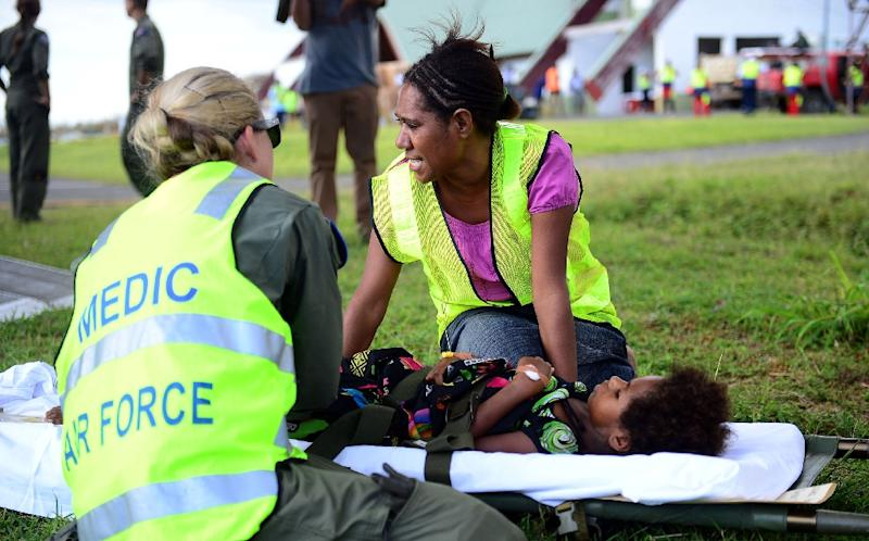 Australian doctors helping in the aftermath of Cyclone Pam give medical aid to a young girl on the Vanuatu island of Tanna on March 18, 2015 (AFP Photo/Jeremy Piper)