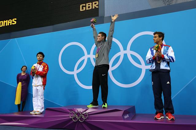 LONDON, ENGLAND - AUGUST 11: Silver medallist Bo Qui of China, gold medallist David Boudia of the United States, and bronze medallist Tom Daley of Great Britain celebrate on the podium during the medal ceremony for the Men's 10m Platform Diving Final on Day 15 of the London 2012 Olympic Games at the Aquatics Centre on August 11, 2012 in London, England. (Photo by Clive Rose/Getty Images)