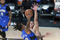 Orlando Magic's Markelle Fultz, left, goes up for a shot as Milwaukee Bucks' Brook Lopez defends during the second half of an NBA basketball first round playoff game Saturday, Aug. 29, 2020, in Lake Buena Vista, Fla. (AP Photo/Ashley Landis)